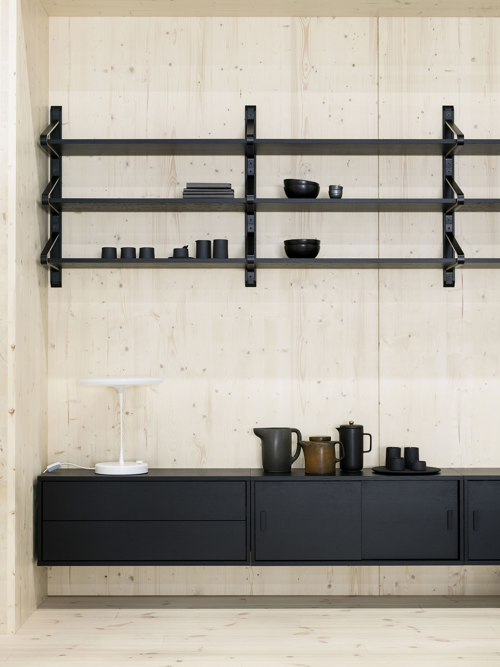 Black shelf system in wooden interior