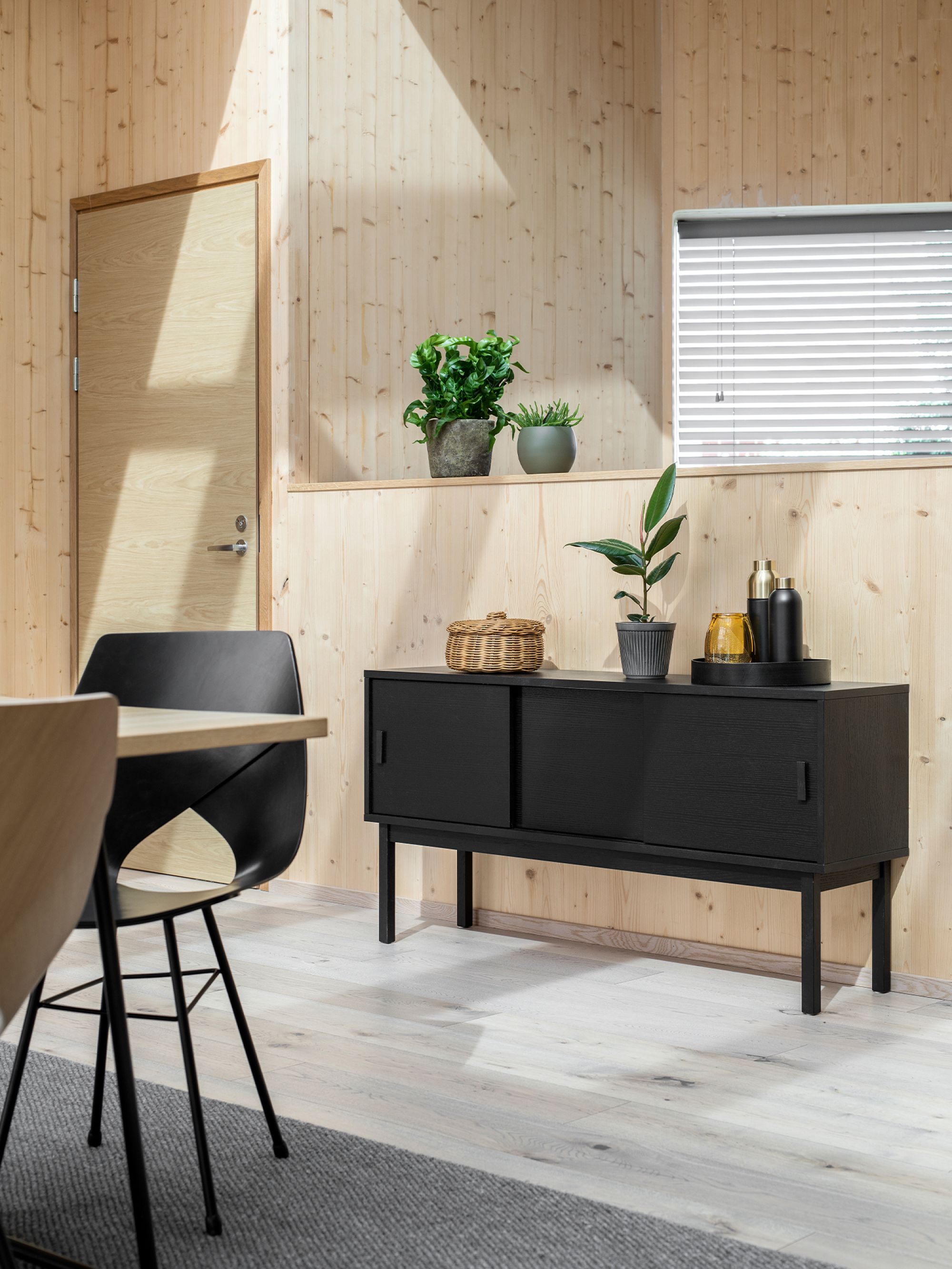 Black cabinet in wooden dining interior